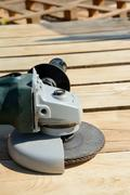 Front part of angle grinder with abrasive disc on planks after work. Stock Photos