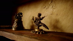 Element of the interior. The stand from natural wood with copper figurines on it Stock Footage