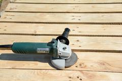 Angle grinder with abrasive disc on planks after work. Stock Photos