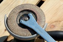 Front part of angle grinder with abrasive disc and spanner after work. - stock photo