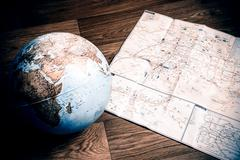 globe and map on the wooden floor - stock photo