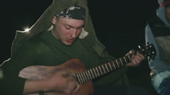 One man playing the guitar at night for the soulmates - stock footage