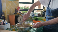 Baby boomer man vigorously and enthusiastically mixing a bowl of matzo balls - stock footage