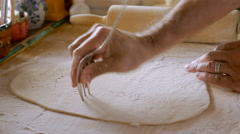 An attractive man poking a fork into dough while making home made matzo Stock Footage