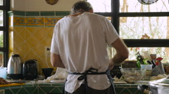 The back of a man chopping and cooking food in his kitchen Stock Footage