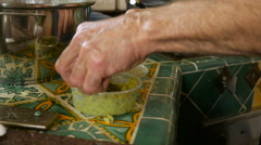 Close up of a man spooning homemade falafel into a pot - stock footage