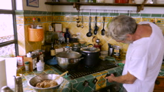 An elderly man lighting a gas stove and checking a pot of steaming food Stock Footage