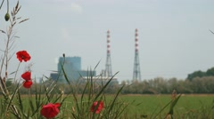 Incineration plant behind some poppies, focus shift Stock Footage