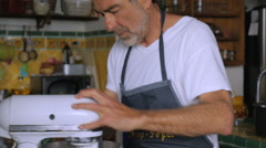 An active senior operates a kitchen mixer in slow motion Stock Footage