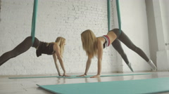 Two Pretty Girls- Aerialist Doing Acrobatic Tricks On Aerial Silks - stock footage