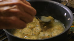 Close up of a man's hand stirring and cooking matzah ball soup on stovetop Stock Footage