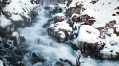 Water in frozen stream. Snowy river in forest in the winter. Long exposure Stock Footage