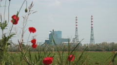 Panoramic view of incineration plant behind some poppies Stock Footage