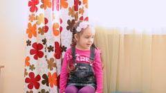 Cute little girl sitting near the window in the kindergarten. Slowmotion Stock Footage