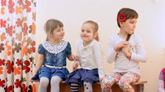 Three cute little girls sitting on a brench and laughing. Slow motion Stock Footage