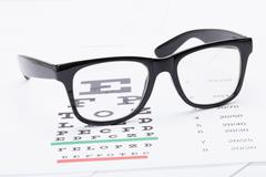 Table for eyesight test with neat glasses over it Stock Photos