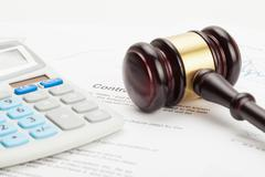 Wooden judge's gavel and calculator over some financial documents Stock Photos