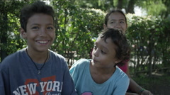 Three smiling kids sitting in the park at Guatemala Arkistovideo