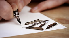 Writting letter with a pen surrounded different pens. Calligraphy lesson. Close - stock footage