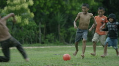 Boys playing with a ball on a wet lawn, Guatemala - stock footage
