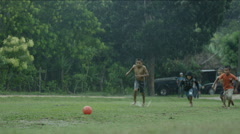 Boys playing with a football on a wet lawn, Guatemala Stock Footage
