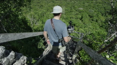 Man with a camera climbing down the steps in forest at Guatemala Stock Footage