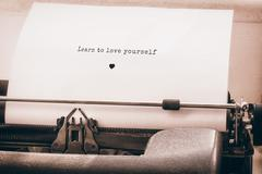 Composite image of learn to love yourself message on a white background Stock Photos