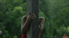Shy girl hiding behind a wooden pole and smiling, Guatemala Stock Footage