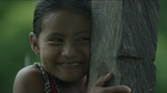 Shy girl holding a wooden pole and smiling, Guatemala Stock Footage