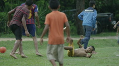 Group of boys playing football on a rainy day, Guatemala Stock Footage