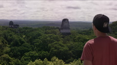 Rear view of a man pointing at Tikal ruins, Guatemala Stock Footage