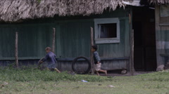 Two boys playing with tire outside a hut in village, Guatemala - stock footage