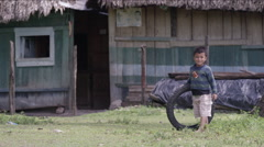Boy playing with a tire outside a hut in village, Guatemala Stock Footage