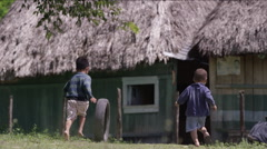 Boys playing with tire outside a hut in village, Guatemala Stock Footage