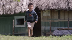 Boy running outside a hut in village, Guatemala Stock Footage