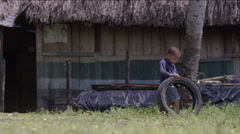 Boy playing with a tire outside a hut in village, Guatemala - stock footage
