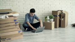 Young boy checking home project on laptop sitting on floor at new home Stock Footage