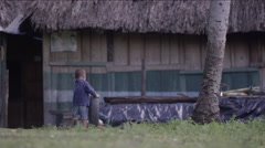 Two boys playing with tire outside a hut in village, Guatemala Stock Footage