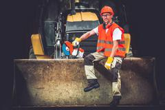 Bulldozer Works Concept. Young Caucasian Men Seating on Bulldozer - stock photo