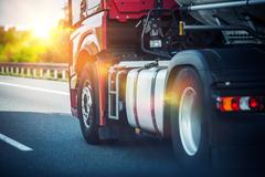 Red Semi Truck Speeding on a Highway. Tractor Closeup. - stock photo