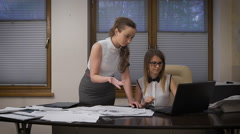 Two young business women working on a serious project. They tense situation - stock footage