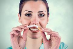 Composite image of close-up portrait of smiling woman holding cigarette - stock photo