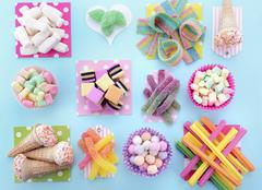Bright Colorful Candy on Pale Bluw Wood Table. Stock Photos