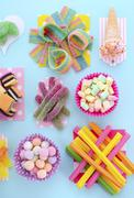 Bright Colorful Candy on Pale Bluw Wood Table. - stock photo