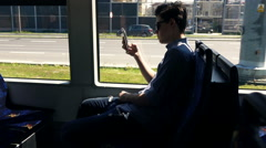 Young boy using smartphone during tram ride in city, super slow motion 240fps Stock Footage
