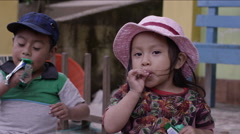 Cute siblings having chocolate together, Guatemala - stock footage