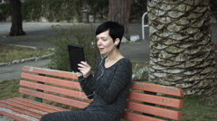 Woman using app on touch screen tablet for video call at playground Stock Footage