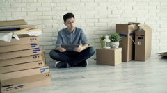 Young boy checking home project on tablet computer sitting on floor at new home Stock Footage