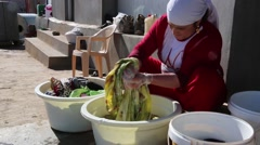 Iraq, February 2016: Iraqi woman cleaning bed clothes in a wash bucket Stock Footage