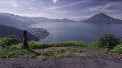 View of beautiful lake and a girl walking on the hill top Stock Footage